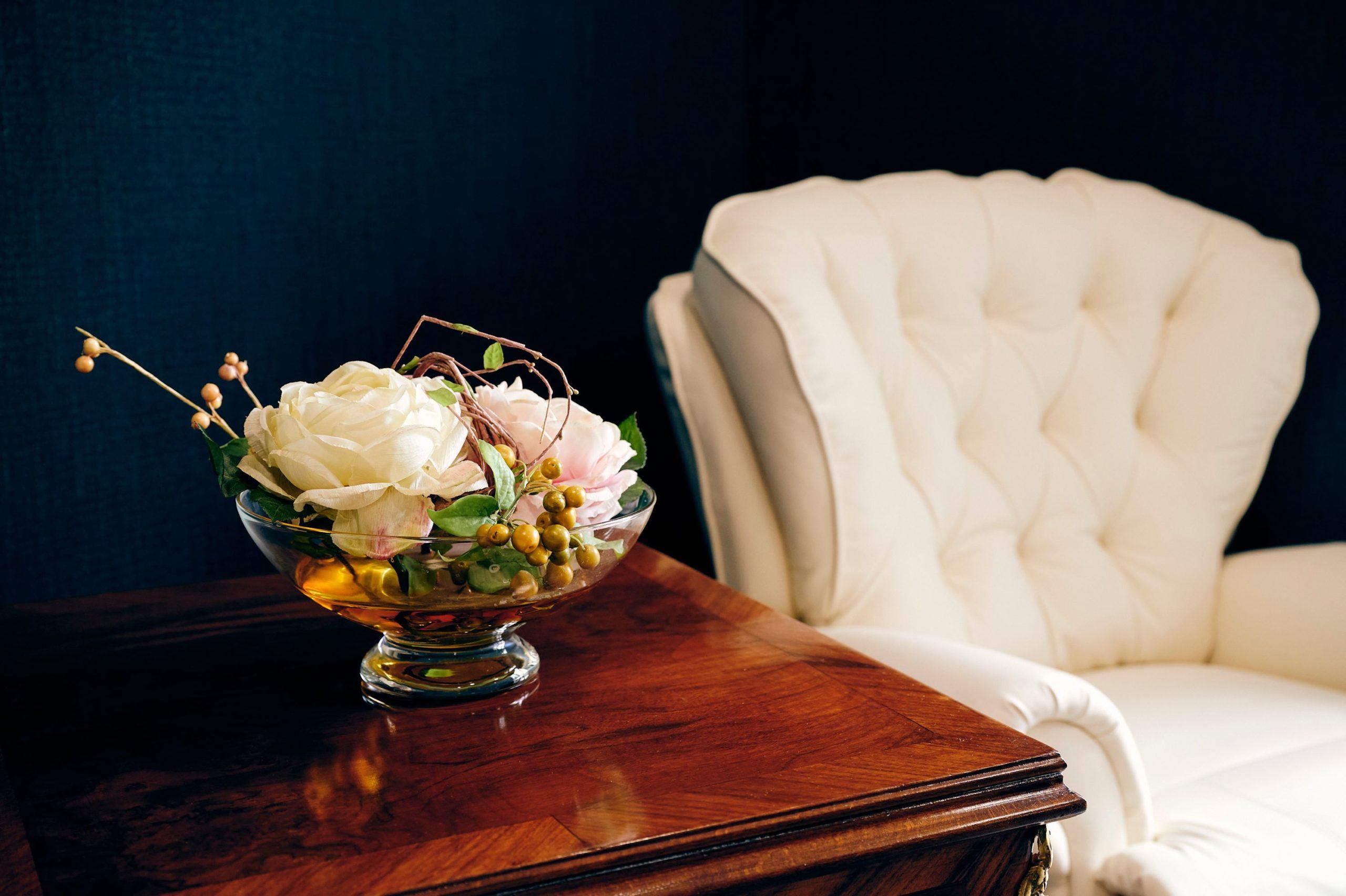 Foto von einem Sessel mit Tisch und Blumenschale im Vordergrund